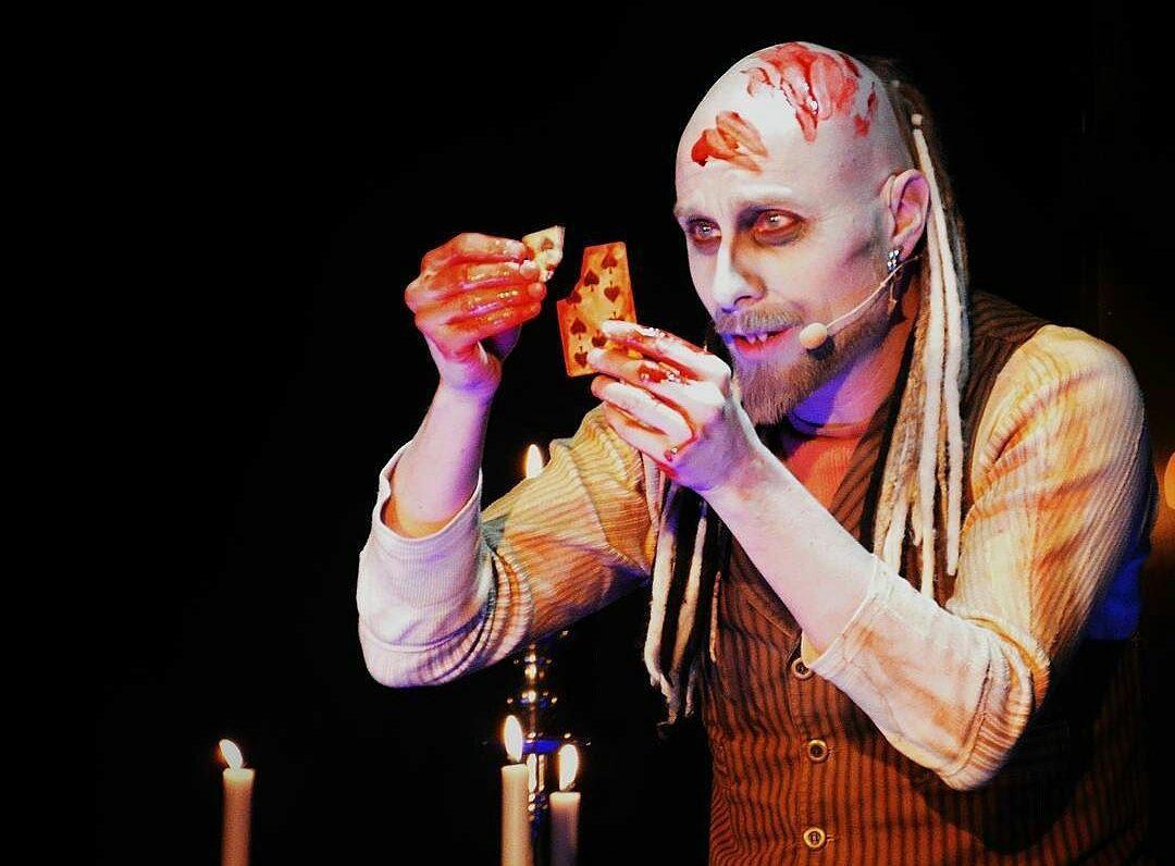 Arkadia som vampyr gräver fram ett kort i magen på en åskådare.